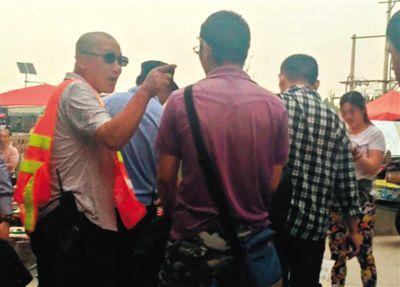 """地铁天通苑北站外的广场上,一名套着""""Police""""(警察)字样背心的人要求摆摊的记者离开,但没驱赶其他摊贩。"""