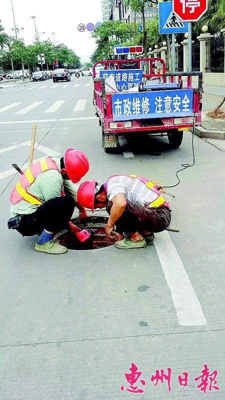 工人在为雨水井加装防坠网。