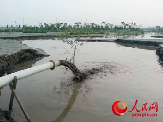 一根白色的管道不断往池塘里排放泥浆