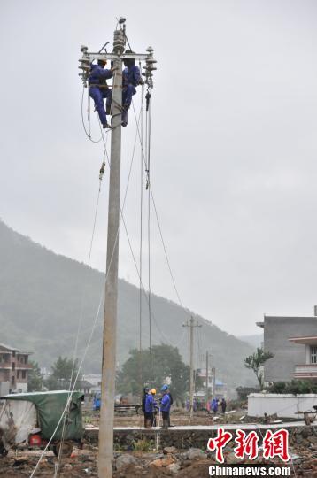 图为电力抢修人员在架线。 詹春艳 摄