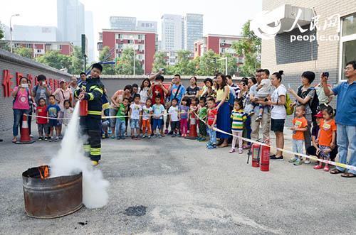 消防战士为家长和孩子展示灭火器材的使用。