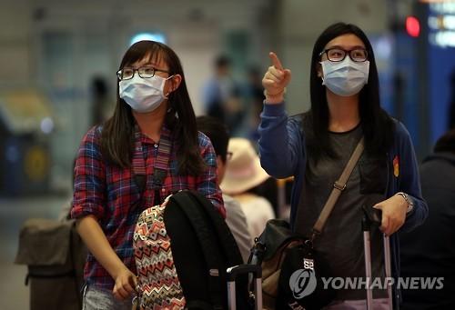 资料图片:1日上午,通过仁川国际机场入境韩国的外国游客大都戴着口罩。(韩联社)