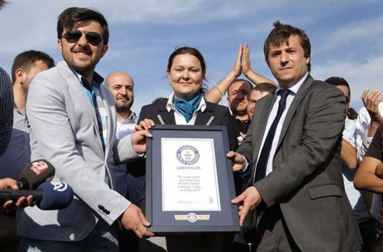 吉尼斯世界纪录官员向海报制作方颁发证书(网页截图)