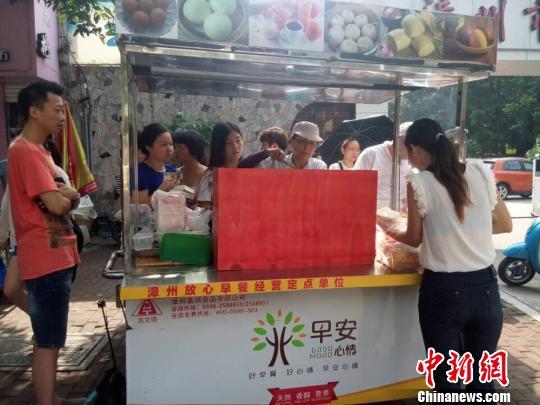 林宗荣夫妇推着早餐车到漳州市青少年宫门口卖台湾早餐。 高淑萍 摄