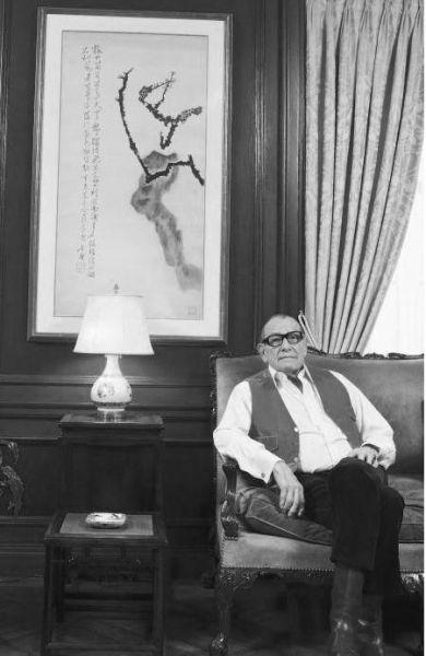 安思远位于其公寓书房,上方悬挂的为石鲁作品《春梅独立》