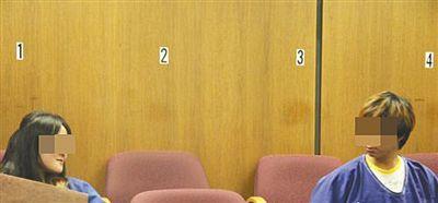 被告人翟某在法庭上跟另一名被告人张某眼神交流。