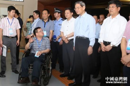 中共中央台办、国务院台办主任张志军与福建省残联副理事长杨小波(坐轮椅者)亲切交流。