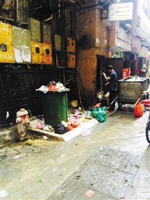 记者日前在沙尾西村看到,环卫工人正在处理被堆放在拐角处的垃圾.
