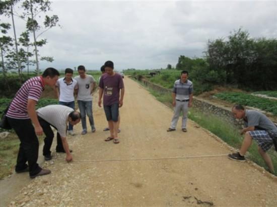 图为现场检查定计村土地整治项目泥结石路面宽度