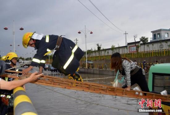 甘肃一公交车被淹路中间 乘客爬消防梯获救