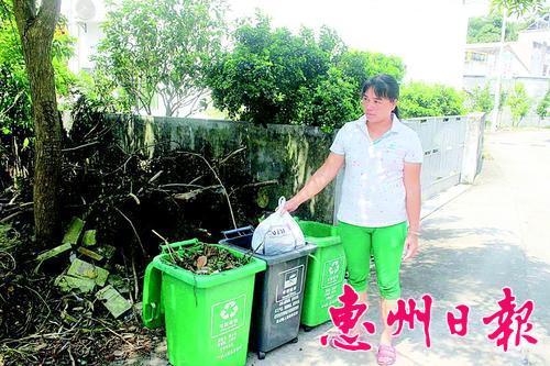 村民把垃圾投入分類垃圾桶。