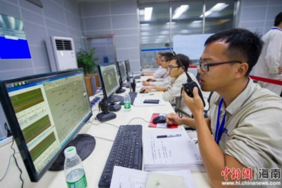 图为7月5日晚,海南国电西南部电厂主控室的技术人员们连夜调试设备。