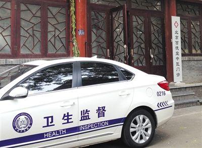 """昨日,""""衛生監督""""執法車輛停靠在""""百德堂""""診所門外。診所大門左側""""北京中研漢唐中醫藥研究中心""""牌匾已被執法人員摘除。 本版攝影新京報記者 尹亞飛 攝"""