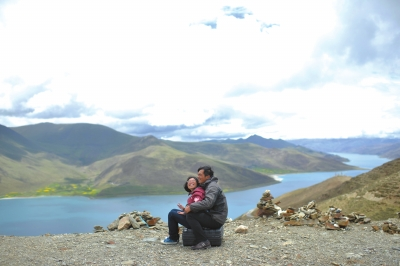 Lai Min and Ding Yizhou cuddle up together to enjoy the scenery at a lake in Tibet on July 9.