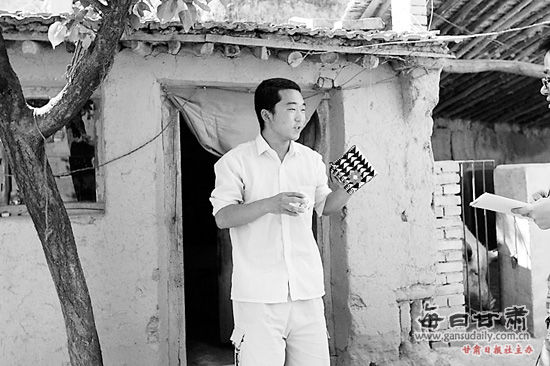 王兆辉拿着自己的储钱罐在土坯房门口,向记者讲述自己的故事。本报记者阎世德摄