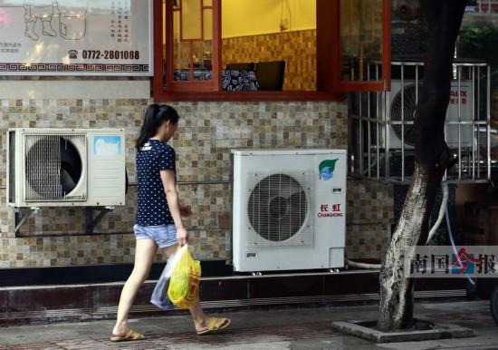 罗池路上,一些饮食店将空调外挂机装在人行道旁.记者颜篁 摄