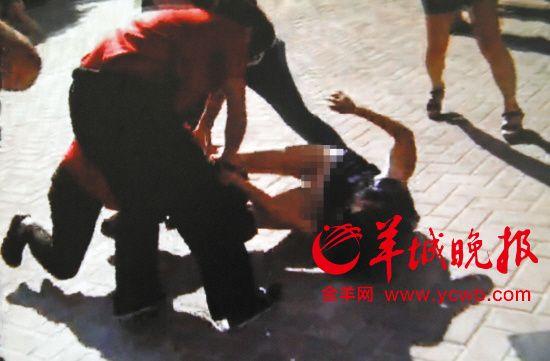 女业主被保安掀翻在地。记者 王俊伟 摄(翻拍视频)