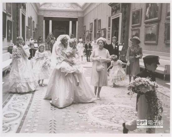 黛安娜王妃穿着美丽的婚纱,抱起小花童,笑容可掬十分亲切。(图片取自metro)