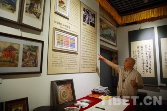 叶星生向中国西藏网记者介绍自己50年艺术展的部分作品,图中上方即为他第一幅作品《情系山茶花》。