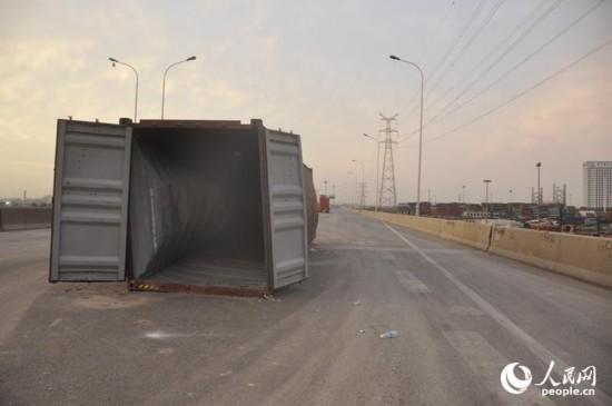 集装箱被冲到了一侧高速路的高架桥上。人民网记者唐述权 摄