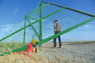 牧民新建的草场围栏大门被盗采者破坏掀翻。