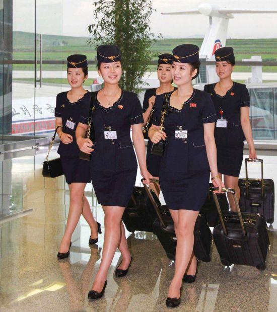 这些空姐身着2013年更换的新制服,胸前带有朝鲜前领导人金日成和金正