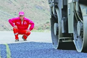 7月29日,达吾列提时刻关注着路面补油的质量。