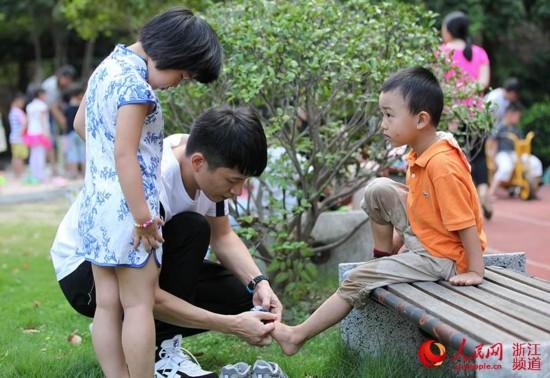 帮助刚玩好游戏的小朋友穿袜子。章勇涛 摄