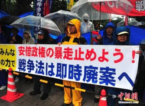 日本民众雨中抗议安保法。