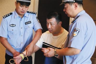 """昨日,福州,公安人员给杨进军戴上手铐。美国首次向中国遣返""""百名红通人员""""。新华社记者 殷刚 摄"""