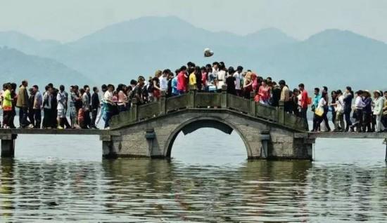 图为杭州西湖断桥游人如织。 如果在假期打算去家喻户晓的旅游名胜地观光的话,那么请你一定要做好挨挤的准备。每个黄金周,故宫、长城、西湖等大家耳熟能详的著名旅游景点,无一不是 人山人海。大家挤在一处,摩肩擦踵,寸步难移。在这种情况下,与其说看风景,还不如说是看人。