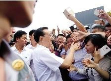 在郑东新区,市民激动地与总理握手
