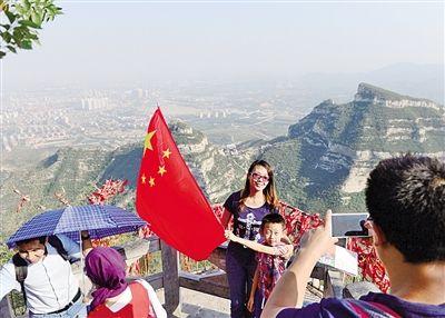 河北石家庄市鹿泉区抱犊寨风景区,游客在山顶展开国旗,为祖国