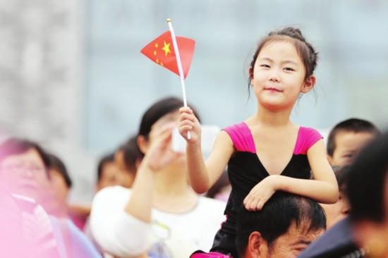 人群中一名女孩挥舞着手中的国旗,喜迎国庆。  侯建平 摄