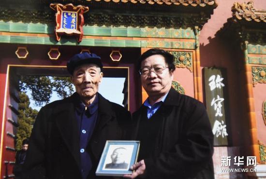 梁金生和他父亲梁匡忠(左)拿着梁金生祖父梁廷炜的照片在故宫珍宝馆前合影(翻拍照片)。