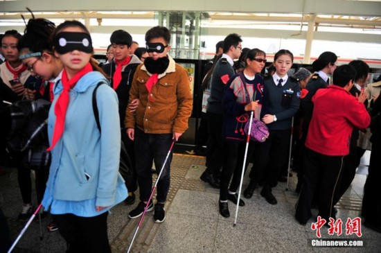高清:昆明盲人坐地铁 高校学生蒙眼陪同