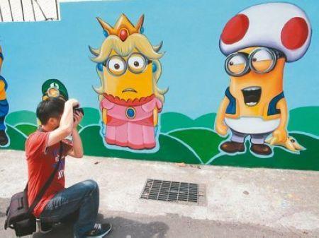 彩绘墙以卡通人物小黄人为主轴,吸引不少游客前往拍照。来源:台湾《联合报》