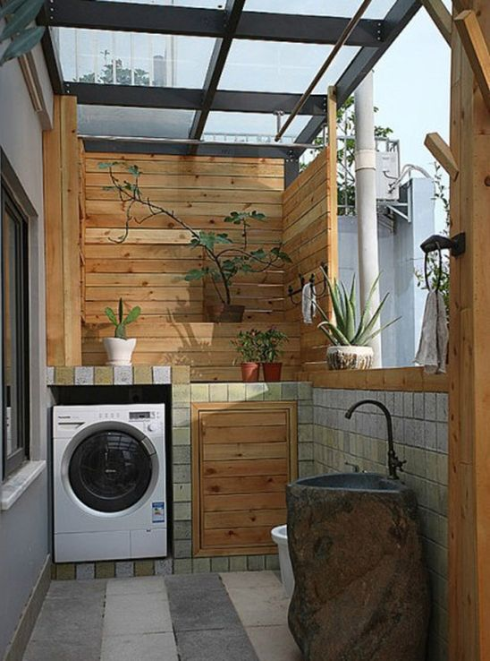 阳台化身洗衣房 小户型空间布局上策 小编的话:巧克力色瓷砖铺贴在石材砌好的台面上,左侧是水池,下方空间可以用作收纳使用,右侧是洗衣机,上方的台面可以随意放置一些装饰物,绿植盆栽也是不错的选择。