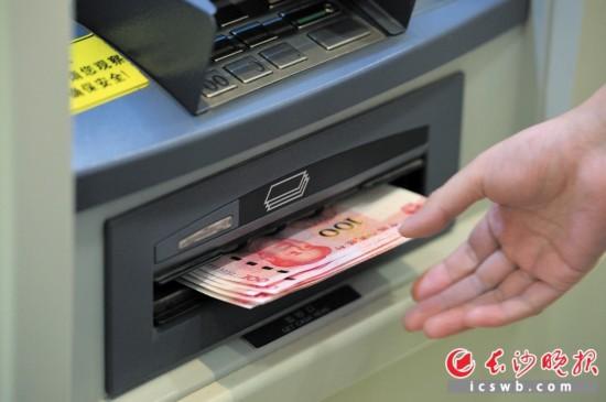市民在银行ATM机上提取新版百元钞票。  新华社发