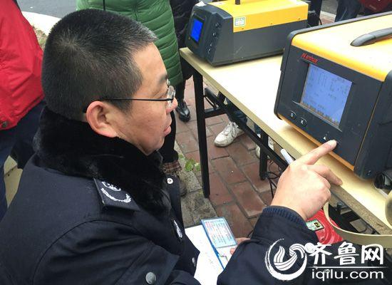 环保部门的工作人员现场对车辆尾气的不透光系数进行检测。