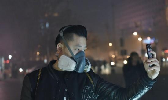 11月30日,北京朝阳区体育馆东路三里屯商务区,一名戴着防毒口罩的