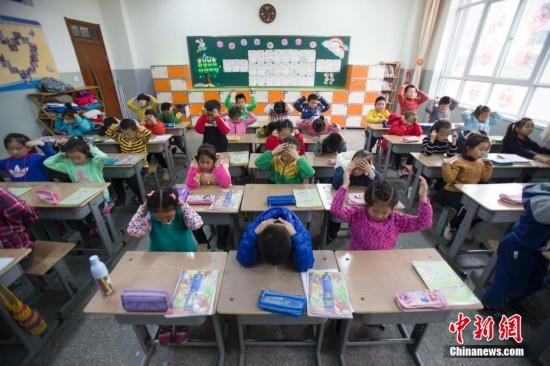 小学生在室内体育课上学做眼保健操. 张云 摄