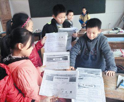 南冈春蕾小学的小学生翻出报纸复印件。