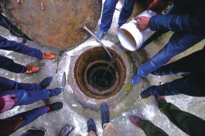 干涸的水井下坑洞暗藏,倒水进去,水很快渗透到地底。