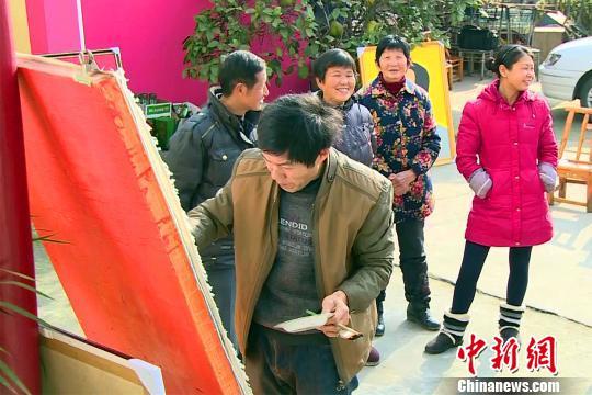 乡亲们到张家发家里来观看画画 江谷洋 摄
