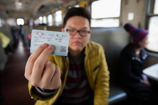 """2016年01月03日,""""火车迷""""李子傲在展示他提前购买的最后一天7102次列车车票。"""