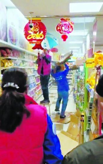 北京东坝一家超市自来水管爆裂员工撑伞护货(图)