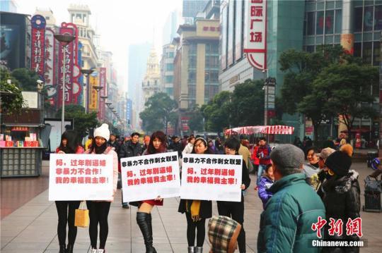"""资料图:2015年2月4日,几位女青年手举标语出现在上海闹市区,无声地抗议亲友的逼婚行为,其标语上写着""""妈,过年回家别逼婚。我的幸福我主宰!""""中新社发 章渝 摄 CNSPHOTO"""