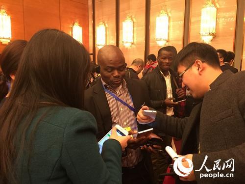 政协新闻发布会结束后,会上获得提问机会的尼日利亚记者Ikenna Emewu被中国记者围住。人民网记者贾�h 摄