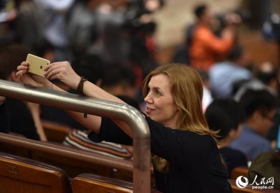 一外国记者正在用手机进行直播。